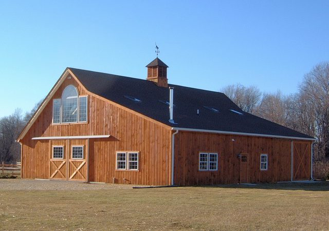 A brown barn with shingle with bay windows