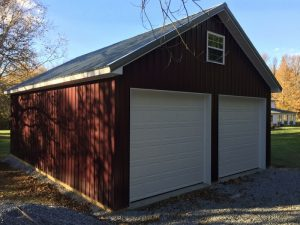 Red Pole Barn with white garage door in CT