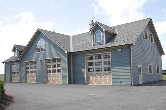 Heron blue horse barn with gray asphalt roof